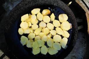 Aufnahme von oben, Kartoffelscheiben in einer schwarzen Pfanne frittiert