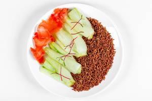 Aufnahme von oben: Teller mit Pak Choi, braunem Reis und eingelegtem Ingwer vor weißem Hintergrund
