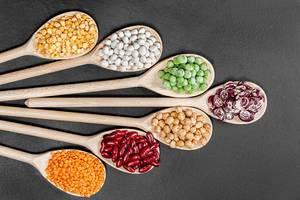 Aufnahme von oben von Linsen, Kichererbsen, Erbsen und Bohnen in verschiedenen Farben auf hölzernen Kochlöffeln vor schwarzem Hintergrund