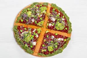 Aufnahme von oben von Pizza mit Mini-Brokkoli und anderen Gemüsesorten vor weißem Hintergrund