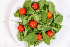 Aufnahme von oben von Teller mit ganzen Cherry-Tomaten auf Babyspinat