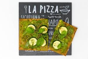 Aufsicht auf die grüne Lizza - eine Vegane Pizza mit Boden aus Chia und Leinsamen Zucchini, Erbsen, grünen Bohnen und frischem Basilikum