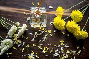 Aufsicht auf ein Duftflakon mit Duftstäbchen und gelben Blumen