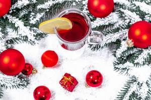 Aufsicht auf ein Glas Glühwein mit Weihnachtsbaumkugeln und Tannenzweigen im Schnee