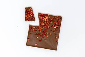Aufsicht auf eine Bio Protein Schokolade mit Erdbeerstückchen mit einer abgebrochenen Ecke auf weißem Hintergrund