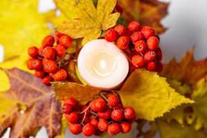 Aufsicht auf eine leuchtende Kerze mit roten Beeren und gelben Blättern als Herbstdekoration