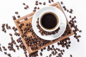 Aufsicht auf eine Tasse Kaffee mit Kaffeebohnen auf einem Holzbrettchen auf weißem Hintergrund