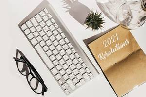 Aufsicht auf Schreibtisch mit Apple Tastatur, Brille, Vorsätze Neujahr 2021, Aloe Pflanze