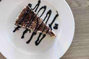 Aufsicht auf Stracciatella Schokoladentorte mit Topping auf weißem Teller