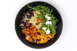 Aufsicht auf vegane Mahlzeit - Hello Fresh Kubanische Quinoa Bowl - mit Rucola mit Sauerrahm, schwarzen Bohnen, Kirschtomaten und zimtigen Süßkartoffeln