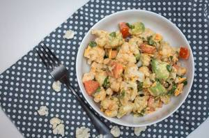 Aufsicht - Blumenkohl Salat, mit Avocado, Möhren und Tomaten in einer Schale auf gepunktetem Platzdeckchen