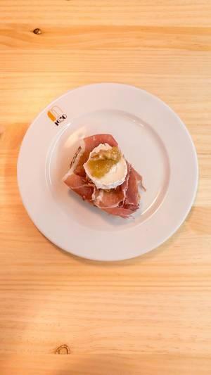Aufsicht - Brot-Häppchen mit Serano Schinken, Weichkäse, Gelee und einer Walnuss auf einem weißen Teller