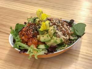 Aufsicht - Ein Salat aus Baby-Spinat, Gurken, Rucola, Avocado, Tomaten, Dressing, Blüten und Sesam in einem ovalen Teller