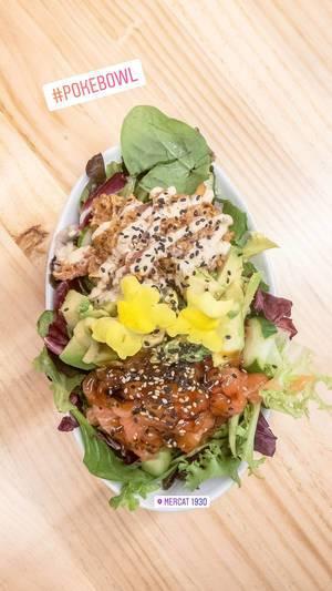 Aufsicht - Ein Salat aus Baby-Spinat, Rucola, Avocado, Tomaten, Dressing, Blüten und Sesam in einem ovalen Teller