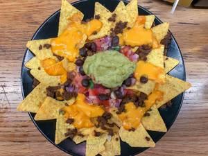 Aufsicht - Eine Portion Nachos mit Käsesauce, Rinderhackfleisch, roten Bohnen, Tomaten, Zwiebeln und Guacamole Avocado-Dip auf einem schwarzen Teller