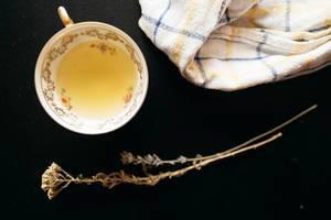 Aufsicht - Eine Tasse Tee mit einem Küchentuch und einem Zweig Lavendel und Kamille auf schwarzem Hintergrund