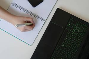 Aufsicht einer Frauenhand, schreibend auf Notizheft, mit Laptop und Smartphone