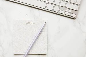 Aufsicht einer To-Do-Liste mit Stift und Tastatur auf Marmor