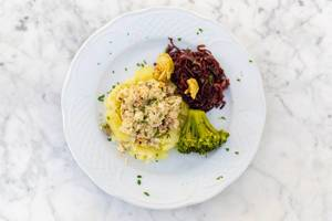 Aufsicht - Fischkuchen auf Kartoffelbett, Broccoli und Rotkohl auf einem weißen Teller