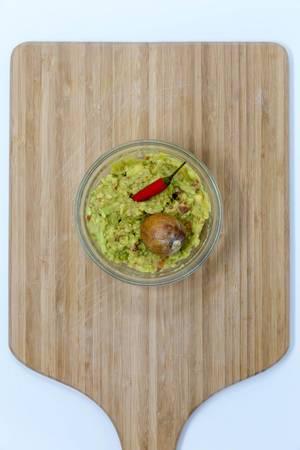Aufsicht - Guacamole Avocado Dip - Brotaufstrich in Schälchen mit roter Chili und Aocadokern