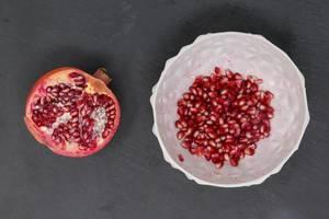 Aufsicht halber Granatapfel mit Granatapfelkernen in weißer Schale auf schwarzer Schieferplatte