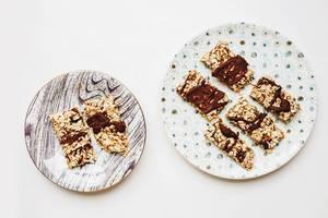 Aufsicht - Hausgemachte Müsliriegel mit Schokolade auf gestreiften und gepunkteten Tellern auf weißem Hintergrund