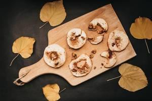 Aufsicht - Nahaufnahme von gebackenen Äpfelscheiben mit Zimt und Walnüssen auf einem Brett und gelben Blättern auf schwarzem Hintergund