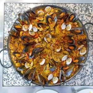 Aufsicht - Paella mit frischen Muscheln in einer Gusseisen-Pfanne