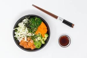 Aufsicht - Poke Bowl Lachs Teriyaki - mit Sushireis, Lachs, Avocado, Krautsalat, Wakame Salat, Wasago, Nori, Teriyaki-Sauce, Soja-Sauce, Sesam und Schnittlauch in einer Schüssel mit Essstäbchen und einer Schüssel Soya-Sauce