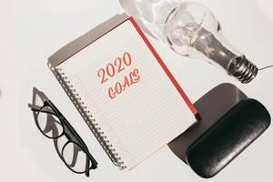 Aufsicht tauf Schreibtisch mit Notizbuch - Ziele 2020 - Brille und Glühbirne