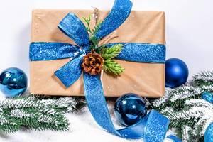 Aufsicht von schneebedecktem Weihnachtsgeschenk in Naturpapier und blauer Schleife, geschmückt mit Tannenzapfen
