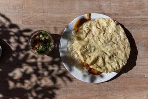 Aufsicht von Tikki Masala Hähnchen mit Reis und Fladenbrot auf weißem Teller mit gemischtem Salat als Beilage