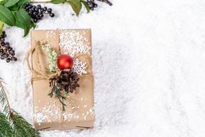 Aufsicht von Weihnachtsgeschenk mit Tannenzapfen und Christbaumkugel geschmückt im Schnee