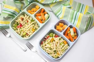 Aufsicht - Zwei kompartimentierte Tupperdosen mit Mittagessen - Nudeln mit Gemüse auf weißem Hintergrund