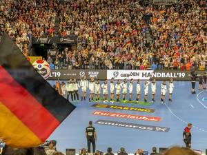 Aufstellung der Deutschen Handballmannschaft in einer Reihe, im Hintergrund Fans auf Tribüne