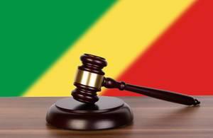 Auktionshammer / Richterhammer auf einem Holzuntergrund, vor der Flagge des Kongo