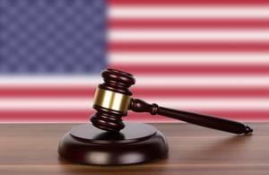 Auktionshammer / Richterhammer auf einem Holzuntergrund, vor der Flagge von Amerika