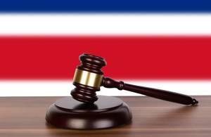 Auktionshammer / Richterhammer auf einem Holzuntergrund, vor der Flagge von Costa Rica