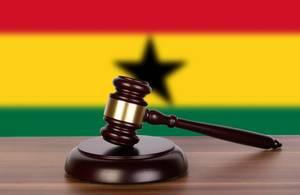 Auktionshammer / Richterhammer auf einem Holzuntergrund, vor der Flagge von Ghana