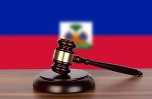 Auktionshammer / Richterhammer auf einem Holzuntergrund, vor der Flagge von Haiti