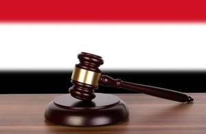 Auktionshammer / Richterhammer auf einem Holzuntergrund, vor der Flagge von Jemen