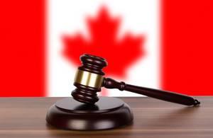 Auktionshammer / Richterhammer auf einem Holzuntergrund, vor der Flagge von Kanada