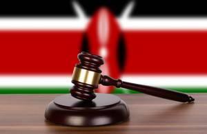 Auktionshammer / Richterhammer auf einem Holzuntergrund, vor der Flagge von Kenia