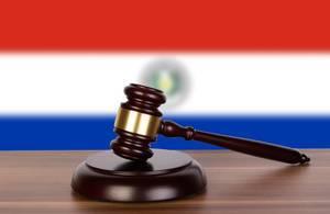 Auktionshammer / Richterhammer auf einem Holzuntergrund, vor der Flagge von Paraguay
