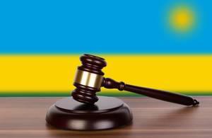 Auktionshammer / Richterhammer auf einem Holzuntergrund, vor der Flagge von Ruanda