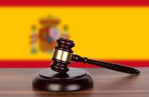 Auktionshammer / Richterhammer auf einem Holzuntergrund, vor der Flagge von Spanien