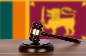 Auktionshammer / Richterhammer auf einem Holzuntergrund, vor der Flagge von Sri Lanka