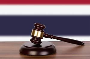 Auktionshammer / Richterhammer auf einem Holzuntergrund, vor der Flagge von Thailand