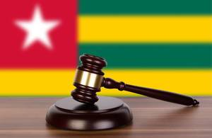 Auktionshammer / Richterhammer auf einem Holzuntergrund, vor der Flagge von Togo