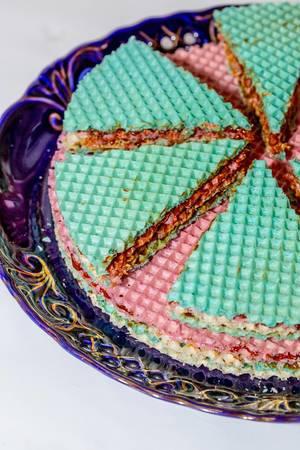 Aus farbigen Waffeln und Kondensmilch zubereiteter Kuchen auf kunstvollem Teller